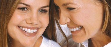 Primer plano de una chica adolescente, a la izquierda, y una mujer madura, a la derecha, ambas se miran sonriendo y llevan un dispositivo de ortodoncia Damon puesto