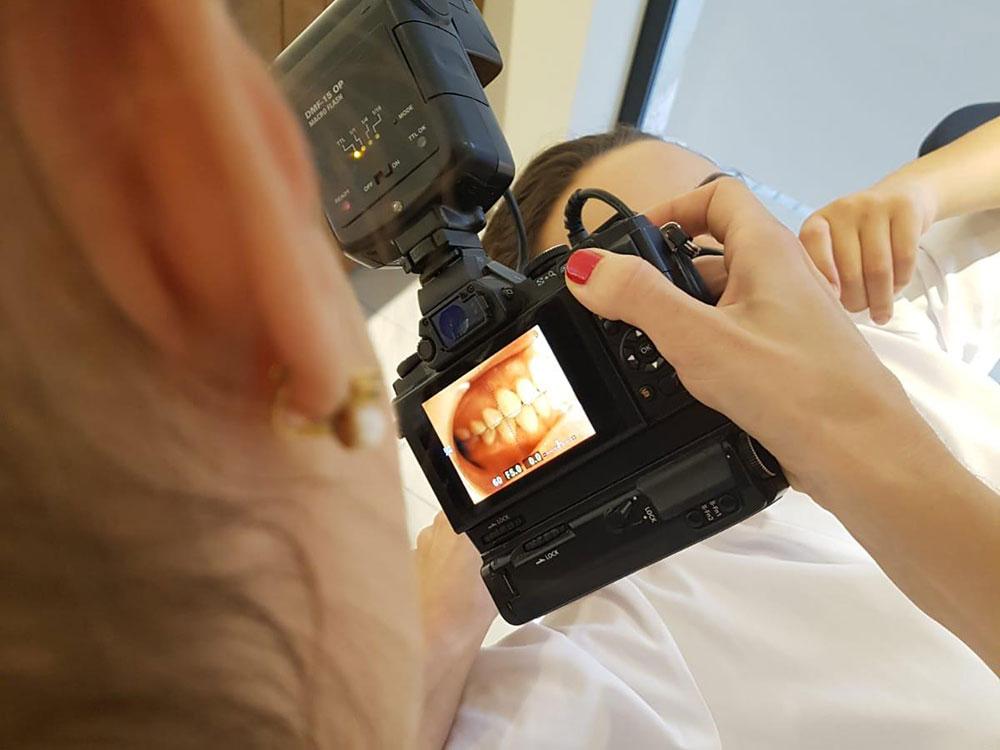 Profesional de estética dental realizando fotografías a un paciente para comenzar con el estudio de su caso
