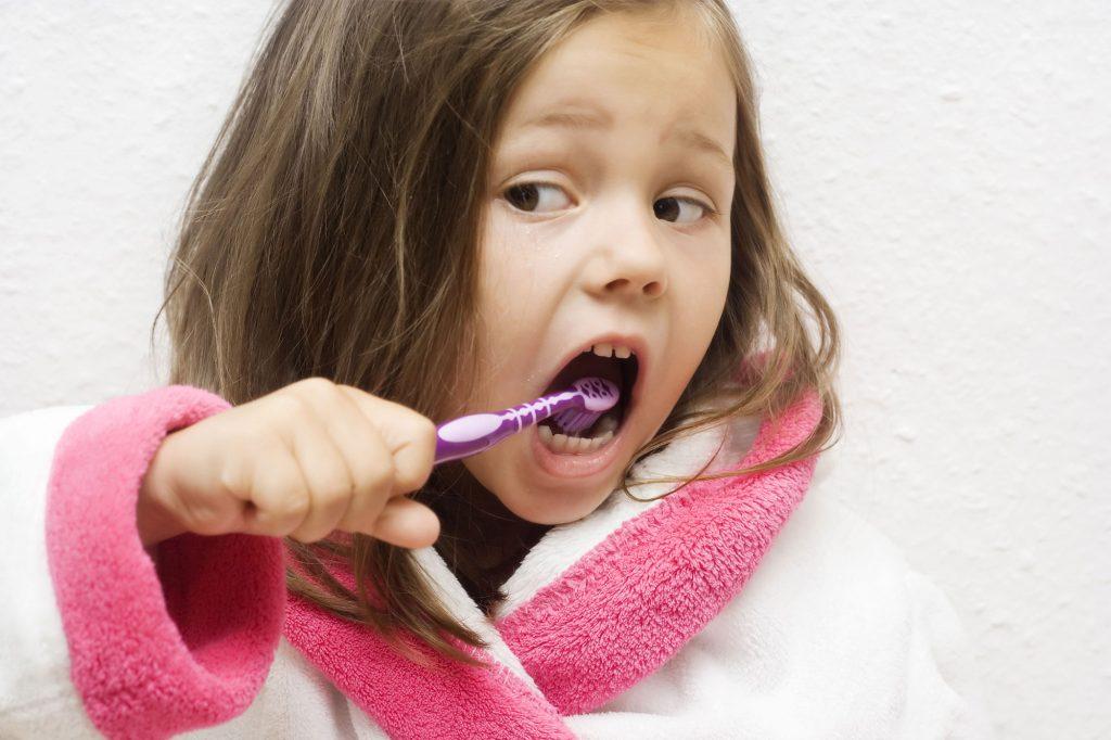 Foto de una niña realizando la higiene bucal diaria en su casa